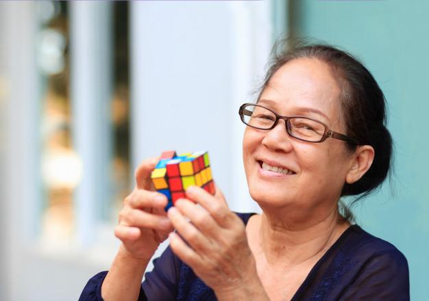 gammel kvinde der løser rubiks cube